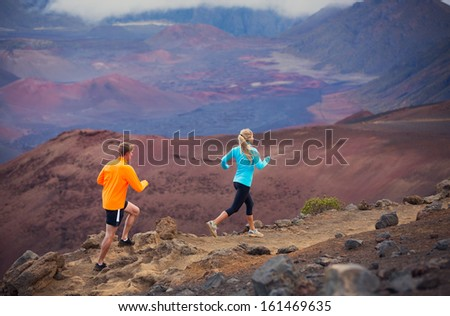 Fitness sport couple jogging outside, training together outdoors. Running on amazing trail at sunset, Dramatic beautiful volcano landscape - stock photo