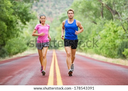Fitness sport couple running jogging outside on road beautiful nature landscape. Runners training together for marathon run. Asian female sports woman and fit male fitness man in full body length. - stock photo