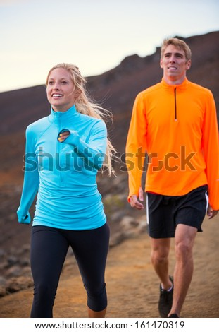 Fitness sport couple walking outside, training together outdoors. Walking on amazing cross country trail at sunset - stock photo