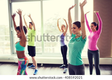 fitness, sport, dance and lifestyle concept - group of smiling people with coach dancing in gym or studio - stock photo
