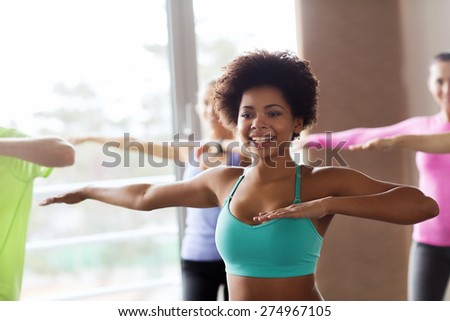 fitness, sport, dance and lifestyle concept - group of smiling people with coach dancing zumba in gym or studio - stock photo