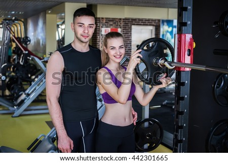 fitness, sport, exercising and diet concept - smiling girl and a man at the gym - stock photo