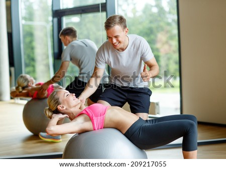 fitness, sport, exercising and diet concept - smiling young woman and personal trainer in gym - stock photo