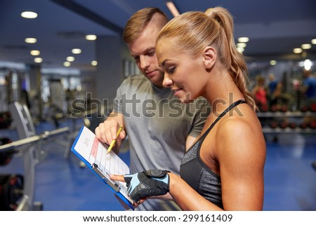fitness, sport, exercising and diet concept - smiling young woman with personal trainer and exercise plan on clipboard in gym - stock photo