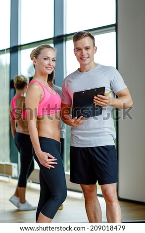 fitness, sport, exercising and diet concept - smiling young woman with personal trainer in gym - stock photo