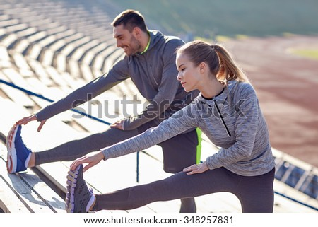 fitness, sport, exercising and lifestyle concept - couple stretching leg on stands of stadium - stock photo