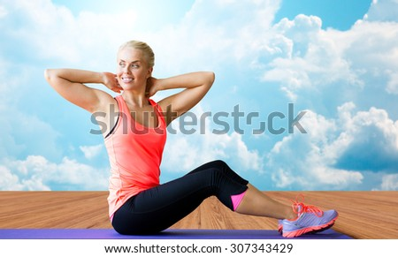 fitness, sport, exercising and people concept - smiling woman doing sit-up on mat over wooden floor and sky with white clouds background - stock photo