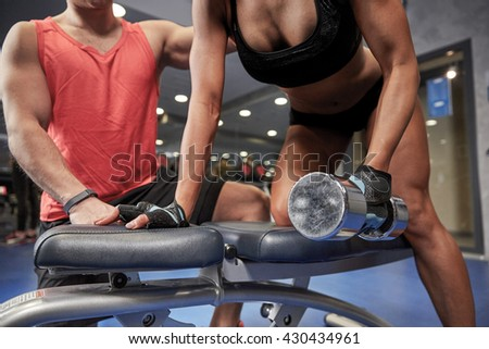 fitness, sport, exercising, bodybuilding and weightlifting concept - close up of young woman and personal trainer with dumbbell flexing muscles in gym - stock photo