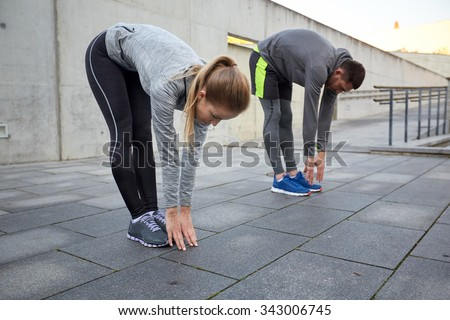 fitness, sport, exercising, people and lifestyle concept - couple stretching and bending forward on street - stock photo