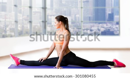 fitness, sport, exercising, stretching and people concept - smiling woman doing splits on mat over gym background - stock photo