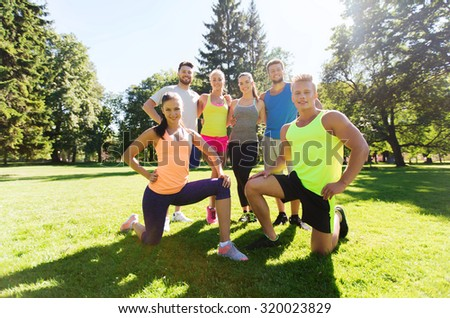 fitness, sport, friendship and healthy lifestyle concept - group of happy teenage friends exercising outdoors - stock photo