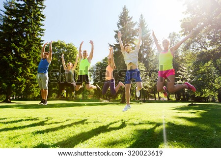 fitness, sport, friendship and healthy lifestyle concept - group of happy teenage friends jumping high outdoors - stock photo