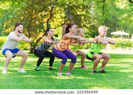 fitness, sport, friendship and healthy lifestyle concept - group of happy teenage friends or sportsmen exercising and doing squats at boot camp - stock photo