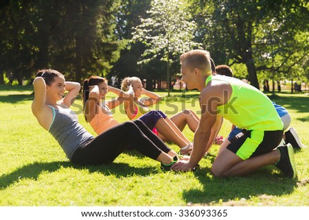fitness, sport, friendship and healthy lifestyle concept - group of happy teenage friends or sportsmen exercising and doing sit-ups at boot camp - stock photo