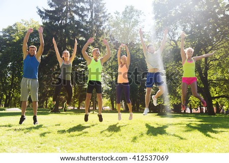fitness, sport, friendship and healthy lifestyle concept - group of happy teenage friends or sportsmen jumping high outdoors - stock photo