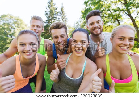 fitness, sport, friendship and healthy lifestyle concept - group of happy teenage friends showing thumbs up outdoors - stock photo