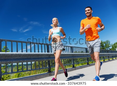 fitness, sport, friendship and healthy lifestyle concept - smiling couple running at summer seaside - stock photo