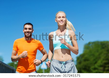fitness, sport, friendship and healthy lifestyle concept - smiling couple running outdoors - stock photo