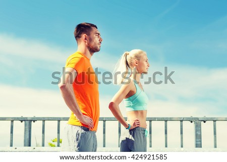 fitness, sport, friendship and healthy lifestyle concept - sporty couple outdoors - stock photo
