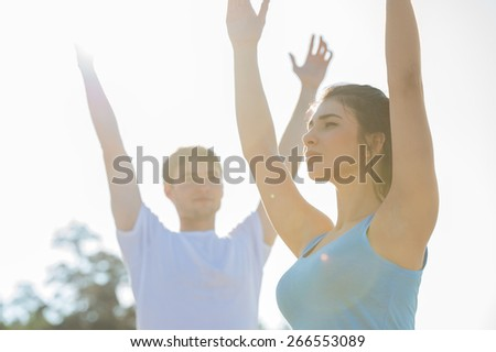 Fitness, sport, friendship and lifestyle concept - smiling couple making meditation yoga exercises on beach at morning - stock photo