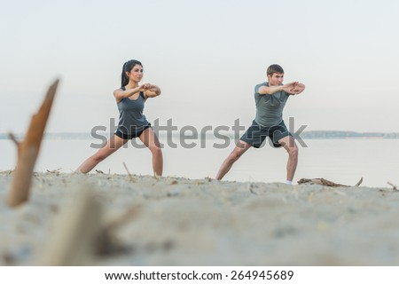 Fitness, sport, friendship and lifestyle concept - smiling couple making stretching yoga exercises on beach at morning - stock photo