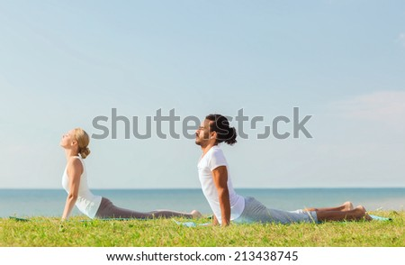 fitness, sport, friendship and lifestyle concept - smiling couple making yoga exercises lying on mats outdoors - stock photo