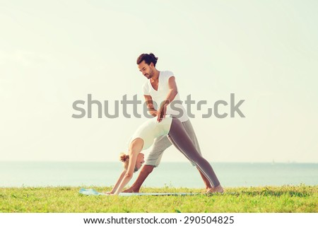 fitness, sport, friendship and lifestyle concept - smiling couple making yoga exercises on mat outdoors - stock photo