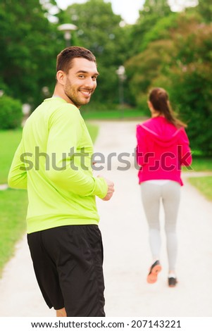 fitness, sport, friendship and lifestyle concept - smiling couple running outdoors - stock photo