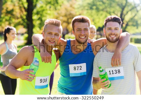 fitness, sport, friendship, marathon and healthy lifestyle concept - group of happy teenage friends or sportsmen with racing badge numbers and water bottles outdoors