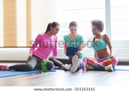 fitness, sport, friendship, technology and lifestyle concept - group of happy women with tablet pc computer in gym - stock photo