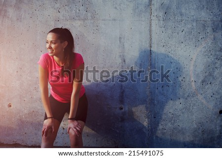 Fitness sport girl resting after intensive evening run, young attractive runner taking break after jogging outdoors, female jogger in bright sportswear smiling looking away, advertising for sports - stock photo