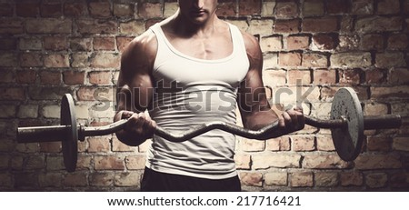 Fitness, sport. Handsome guy with barbell - stock photo