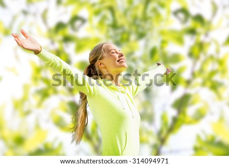 fitness, sport, happiness and people concept - happy woman raising hands over green tree leaves background - stock photo