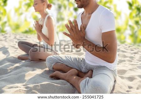 fitness, sport, meditation and lifestyle concept - smiling couple making yoga exercises sitting outdoors - stock photo