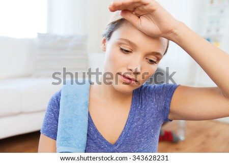 fitness, sport, people and healthy lifestyle concept - close up of tired woman with towel wiping sweat after exercising at home - stock photo