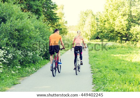 fitness, sport, people and healthy lifestyle concept - happy couple riding bicycle outdoors at summer from back