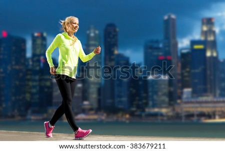 fitness, sport, people and healthy lifestyle concept - happy woman jogging over city street background - stock photo