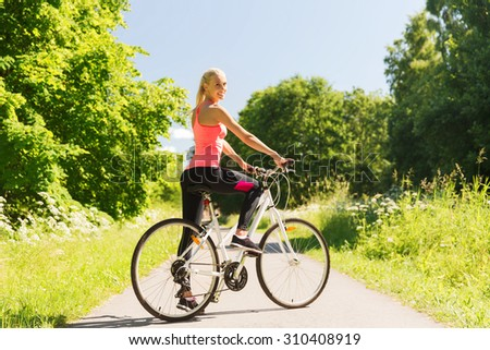 fitness, sport, people and healthy lifestyle concept - happy young woman riding bicycle outdoors - stock photo