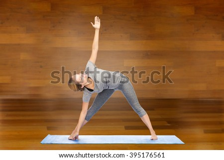 fitness, sport, people and healthy lifestyle concept - woman making yoga triangle pose on mat over wooden room background