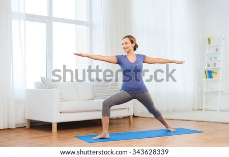 fitness, sport, people and healthy lifestyle concept - woman making yoga warrior pose on mat - stock photo
