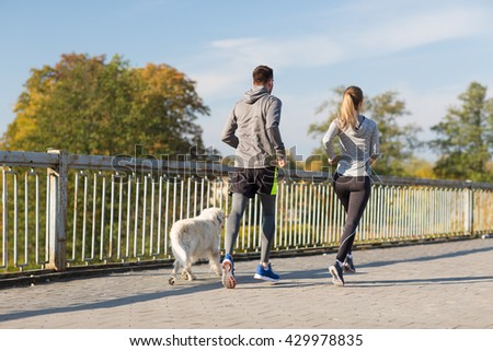 fitness, sport, people and jogging concept - couple with dog running outdoors - stock photo