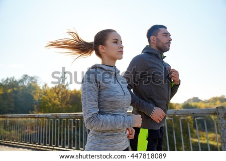 fitness, sport, people and jogging concept - happy couple running outdoors - stock photo