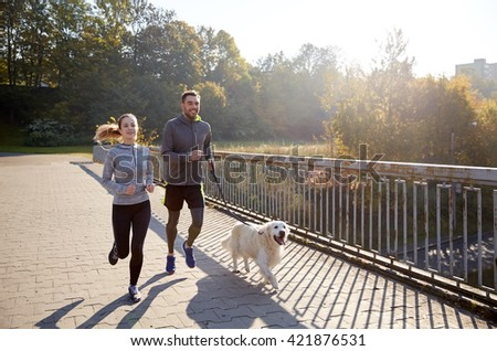 fitness, sport, people and jogging concept - happy couple with dog running outdoors - stock photo