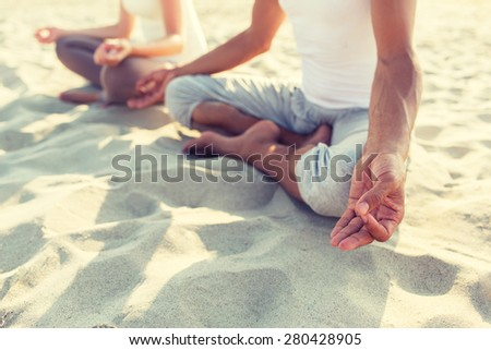 fitness, sport, people and lifestyle concept - close up of couple making yoga exercises sitting on pier outdoors - stock photo