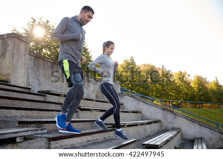 fitness, sport, people and lifestyle concept - couple running downstairs on stadium - stock photo