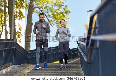 fitness, sport, people and lifestyle concept - happy couple running downstairs in city - stock photo