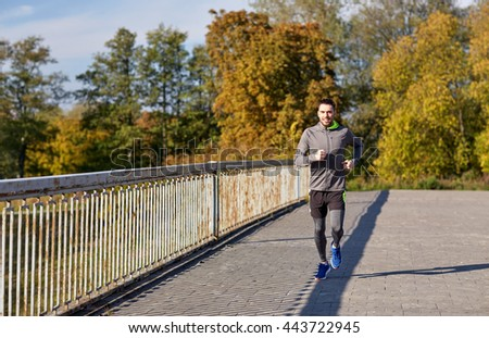 fitness, sport, people and lifestyle concept - happy young man running over city bridge - stock photo