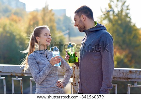fitness, sport, people and lifestyle concept - smiling couple with bottles of water outdoors - stock photo
