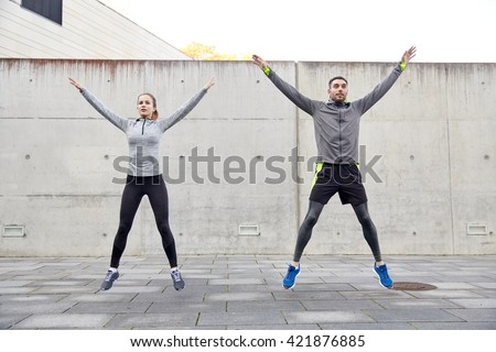fitness, sport, people, exercising and lifestyle concept - happy man and woman doing jumping jack or star jump exercise outdoors - stock photo