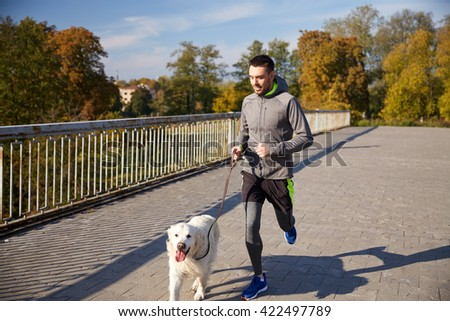 fitness, sport, people, pets and jogging concept - happy man with labrador retriever dog running outdoors - stock photo